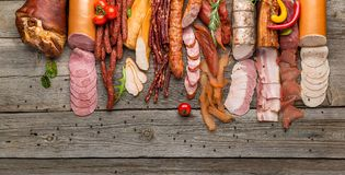 Assortment of cold meats, variety of processed cold meat products. On a wooden background stock photography