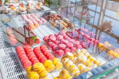 Assortment of colorful macaroons on cafe showcase. Variety of macaron flavours. Sweet almond cakes in store. stock photos