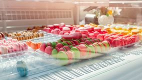 Assortment of colorful macaroons on cafe showcase. Variety of macaron flavours. Sweet almond cakes in store. stock photo