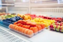 Assortment of colorful macaroons on cafe showcase. Variety of macaron flavours. Sweet almond cakes in store royalty free stock photo