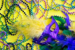Assortment of colorful Mardi Gras decorations. An assortment of colorful decorations for the Mardi Gras festival on a yellow background, including Venetian mask stock images