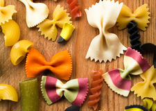 Assortment of colorful pasta on wooden background,italian food Stock Photos