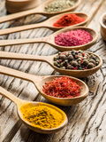 Assortment of colorful spices in the wooden spoons. Royalty Free Stock Photography
