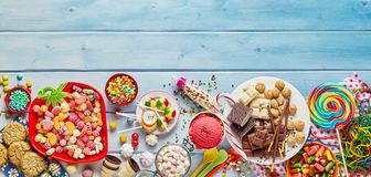 Assorted colourful party sweets with copy space. An assortment of colourful, festive sweets, ice-cream and candy on a timber table with copy space stock photos