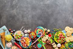 Assortment of colourful sweets with copy space. An assortment of colourful, festive sweets, ice-cream and candy on a dark, rustic background with copy space Stock Photos