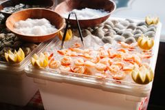 An assortment of cooked shrimp and raw clams on ice garnished wi. Cooked shrimp and raw clams on ice garnished with lemon Stock Photo