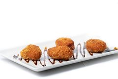 Assortment of croquettes with a vinaigrette on a white rectangular plate royalty free stock images
