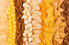 Assortment crunchy snacks - popcorn, nachos, croutons, corn sticks, potato chips as decorative background, top view, closeup. Royalty Free Stock Photography