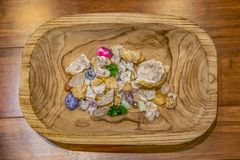 Assortment of crystals and stones of different colors and textures in a carved wooden bowl sitting on a wood plank surface - top royalty free stock photo