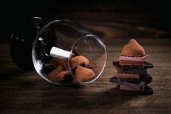 Assortment of dark and milk chocolate stack, truffles. Sweets in a glass on dark rustic wooden table. Selective macro focus. Sweets and chocolate background stock image