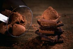 Assortment of dark and milk chocolate stack, truffles. Sweets in a glass. Chocolate with cocoa powder on dark rustic wooden table. Selective macro focus royalty free stock photo
