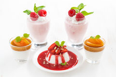Assortment of desserts with cream jelly and fresh berries. On white table, horizontal royalty free stock images