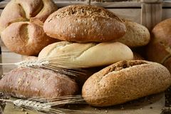 Assortment of different bread rolls. Closeup of an assortment of different bread rolls and some wheat ears on a rustic wooden table Stock Image