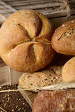 Assortment of different bread rolls. Closeup of an assortment of different bread rolls and some wheat ears on a rustic wooden table Stock Photography