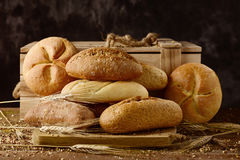 Assortment of different bread rolls. Closeup of an assortment of different bread rolls and some wheat ears on a rustic wooden table royalty free stock images