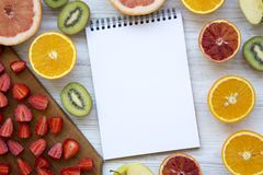 Assortment of different colorful fruits with a notebook, top view. Flat lay royalty free stock image