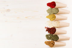 Assortment of different colorful powder seasoning close-up in paper corners on white wooden board with copy space. Stock Photography