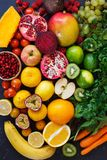 Assortment of different fruits and vegetables in rainbow colors. On dark rustic surface, Healthy eating background royalty free stock photo