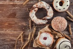 Assortment of different kind of cereal bakery: donuts and cracknel on old wooden background royalty free stock photo