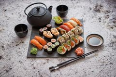 Assortment of different kinds of sushi rolls placed on black stone board royalty free stock photo