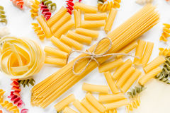 Assortment of different shape italian pastas on white background top view Stock Photography