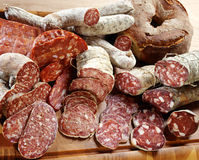 Assortment of different sliced salamis. Assortment of different fresh thinly sliced spicy salami sausages on a wooden board with the remainder of each salami Royalty Free Stock Photo