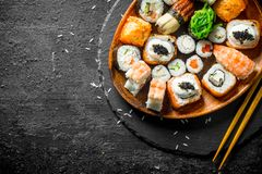 Assortment of different sushi rolls on a plate with chopsticks. On black rustic background stock photos