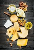 Assortment of different types of cheese with grapes and white wine. On a wooden background royalty free stock images