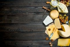 Assortment of different types of cheese with grapes and white wine. On a wooden background royalty free stock image