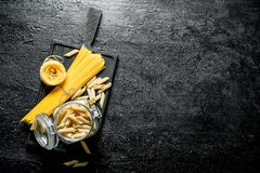 Assortment of different types of pasta dry on a cutting Board and in a glass jar royalty free stock photo