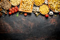 Assortment of different types of raw pasta with mushrooms, tomatoes and garlic. On dark rustic background royalty free stock photography