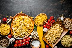 Assortment of different types of raw pasta with mushrooms, tomatoes and garlic. On dark rustic background royalty free stock photos