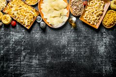Assortment of different types of raw pasta. On rustic background stock photo