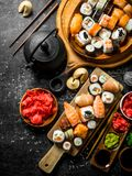An assortment of different types of sushi and rolls. On dark rustic background royalty free stock images