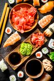 Assortment of different types of sushi, rolls and maki. On rustic background royalty free stock images