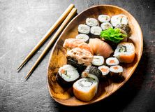Assortment of different types of sushi, rolls and maki on a wooden plate. On dark rustic background royalty free stock photo