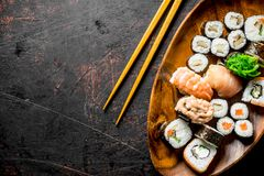 Assortment of different types of sushi, rolls and maki on a wooden plate. On dark rustic background stock images