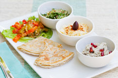 Assortment of dips: hummus, chickpea dip, tabbouleh salad, baba ganoush and flat bread, pita on a plate Stock Images