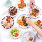 Assortment of dishes: satay with peanut butter sauce, fried wonton, grilled chicken and duck, sauteed vegetables, fried rice, and Stock Image