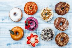 Assortment of donuts for any taste, on old wood background. Space for text. Top view royalty free stock photo