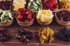 Assortment of dried fruits closeup on brown wooden background. Royalty Free Stock Images