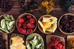 Assortment of dried fruits in spoons, bowls on brown wooden background. Royalty Free Stock Photography