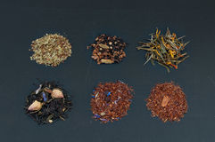 Assortment of dried teas on dark background. Different tea types: green tea, black tea, floral tea and herbal Royalty Free Stock Photo