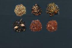 Assortment of dried teas on dark background. Different tea types: green tea, black tea, floral tea and herbal Stock Photo