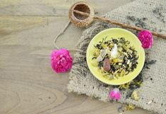 Assortment of dry flower tea in plate with shaku on wooden background. Assortment of dry flower tea in plate with shaku on wooden table Royalty Free Stock Image