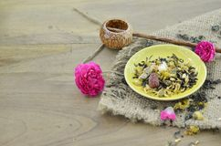 Assortment of dry flower tea in plate with shaku on wooden background. Assortment of dry flower tea in plate with shaku on wooden table Royalty Free Stock Photo