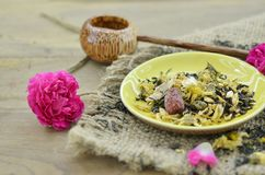 Assortment of dry flower tea in plate with shaku on wooden table. Assortment of dry flower tea in plate with shaku on wooden background Stock Photos