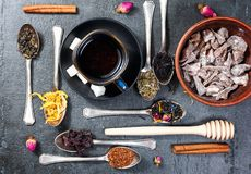 Assortment of dry tea and cup of hot tea. Green tea, black tea, green tea, rooibos, dry rose buds in spoons. Royalty Free Stock Image