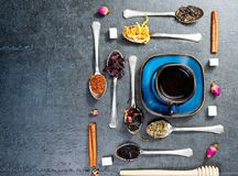 Assortment of dry tea and cup of hot tea. Green tea, black tea, green tea, rooibos, dry rose buds in spoons. Stock Images