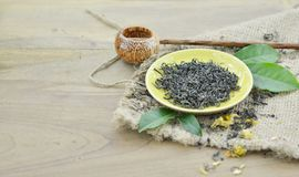 Assortment of dry tea in plate with shaku on wooden background. Assortment of dry tea in plate with shaku on wooden table Royalty Free Stock Image